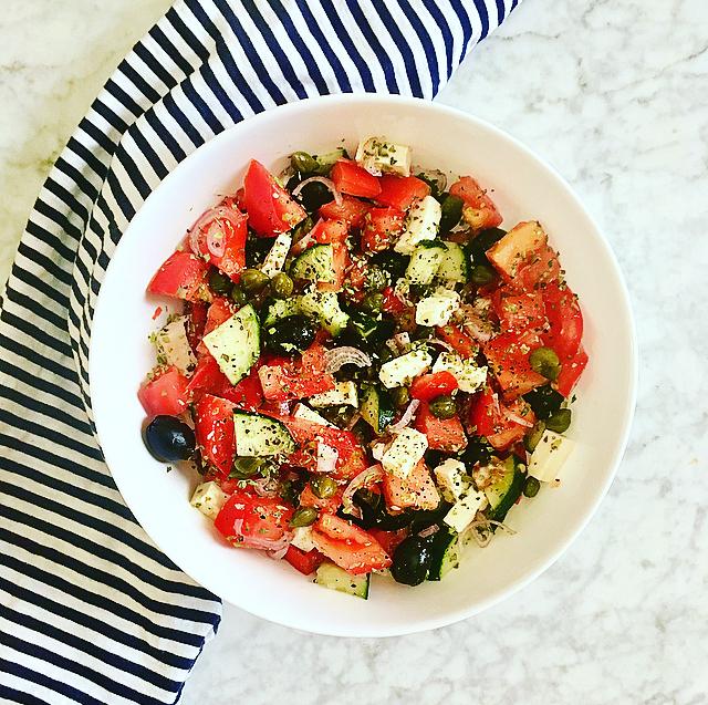 Griekse salade: klassieker met tomaat, feta, zwarte olijf, rode ui, kappertjes en oregano. Meer heb je niet nodig voor een heerlijke salade!