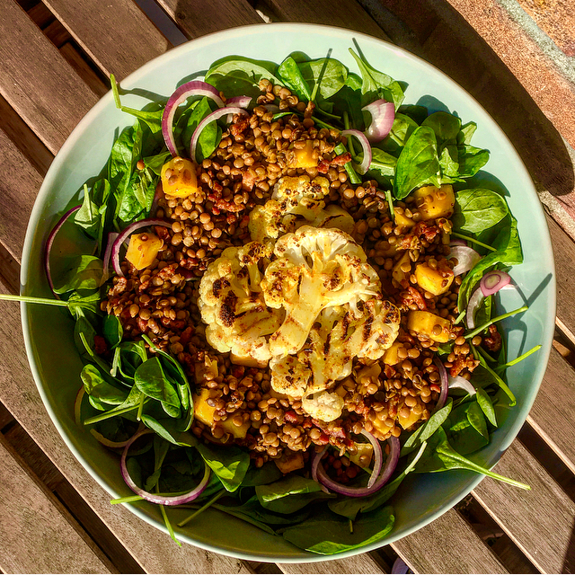 Salade met gegrilde bloemkool, mango, linzen & bacon: een heerlijk kruidige bloemkoolsalade met zoete mango en zoute spekjes.