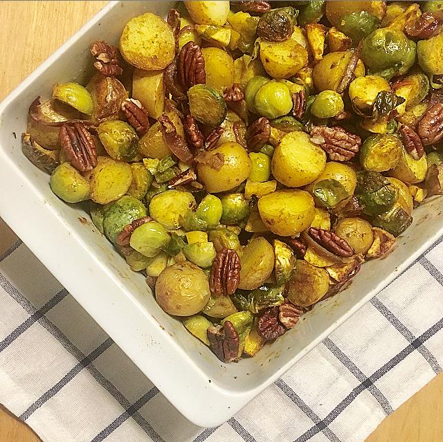Spruitjesschotel met kerrie: verrassende vega ovenschotel met geroosterde spruitjes, aardappeltjes en pecannoten. Hiermee krijg je zelfs de grootste spruitjeshater om!