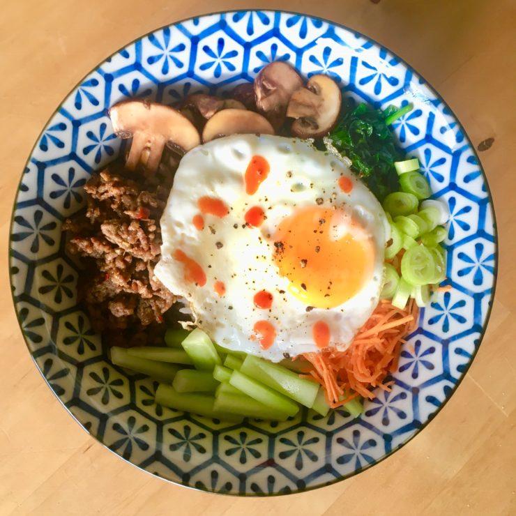 Koreaanse bibimbap: een heerlijke rijstbowl met verschillende groenten, spicy rundvlees en een spiegeleitje. Aziatisch smullen!